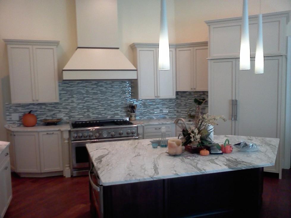 New kitchen with granite slab countertop and mosaic glass backsplash
